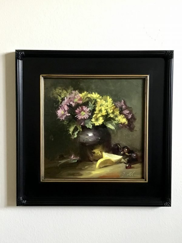A photo of a framed original oil painting on panel of a still life painting of daisies with lemons and grapes.