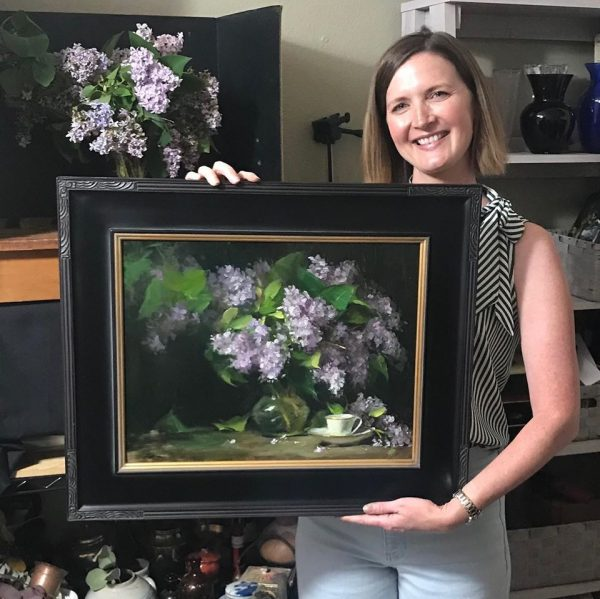 A photo of artist Kelli Folsom holding her original oil painting on panel of a floral still life of lilacs in a glass vase with a white teacup.