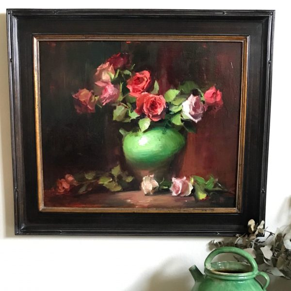 A photo of a framed original oil painting on linen of a still life painting of red and coral roses in a green jar.