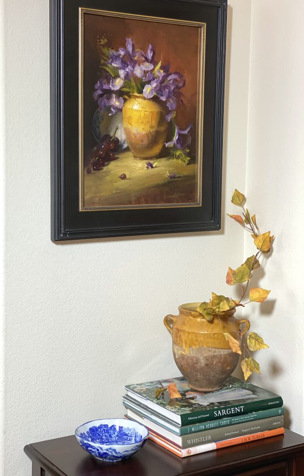 An original oil painting of a still life titled purple irises and a yellow Confit Jar by Kelli Folsom pictured here in a home with art books and blue and white porcelain