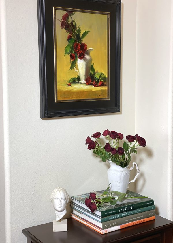 A photo of an original oil painting of a still life featuring red rose spray and white porcelain by Kelli Folsom framed in black and gold. Pictured in a home with Sargent books and a classical art bust sculpture.