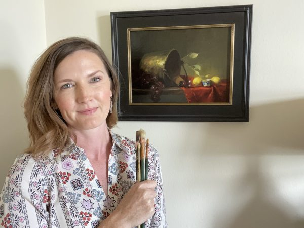 A photo of the artist Kelli Folsom standing in front of her original oil painting of a still life featuring an antique brass bucket with lemons, blue and white porcelain and a red cloth, a very traditional Dutch Masters Still Life