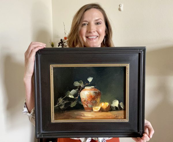 A photo of artist Kelli Folsom holding her original still life painting featuring an orange ginger jar with leaves in fall colors