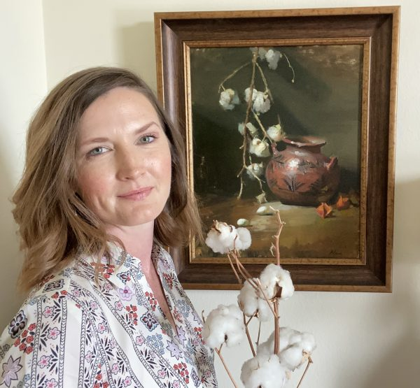 A photo of the artist Kelli Folsom standing in front of her original art featuring a southwestern style still life with Native American Pottery and Cotton Ballsin the Dutch Old Masters light and shadow tradition.