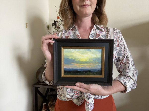 Kelli Folsom with her original oil painting of a Sunrise day number one oil on panel.