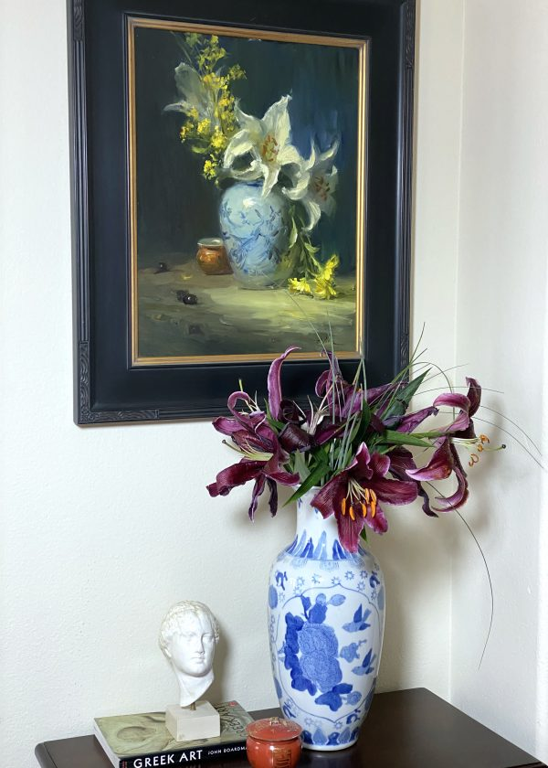 An original oil painting of a still life titled Chinese Ginger Jar with White Lilies by Kelli Folsom pictured here in her home with porcelain and a bust